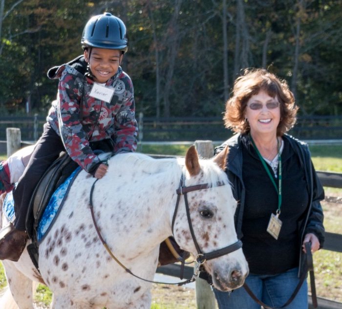 Fieldstone Farm volunteer with student on horse